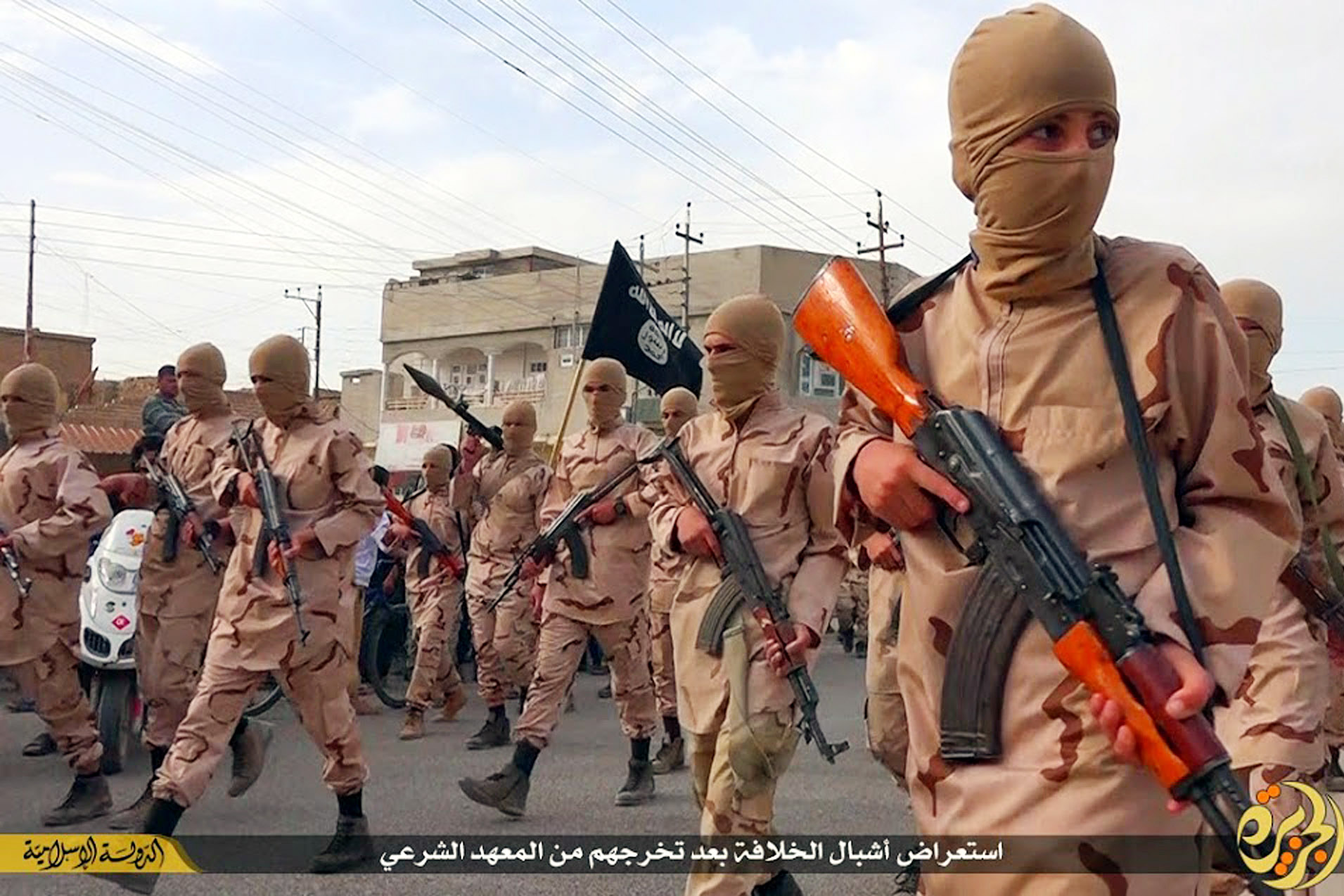 """ADVANCE FOR USE SUNDAY, JULY 19, 2014 AT 1 P.M. EDT (17:00 GMT) AND THEREAFTER - In this photo released on April 25, 2015 by a militant website, which has been verified and is consistent with other AP reporting, young boys known as the """"caliphate cubs"""" hold rifles during a parade after graduating from a religious school in Tal Afar, near Mosul, northern Iraq. The Syrian Observatory for Human Rights, a Britain-based outfit that follows the Syrian war, said it documented at least 1,100 Syrian children under 16 who joined IS so far this year, many of whom were then sent to fight in Syria and Iraq. (Militant website via AP)"""