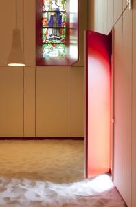 A destra, un ingresso; di fronte una vetrata istoriata.