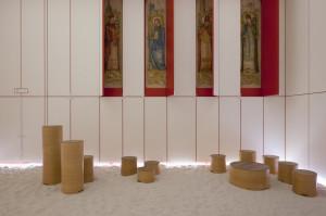 Immagini di santi in evidenza dietro i pannello aperti; le sedute disposte sulla bianca sabbia.